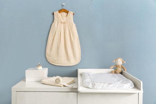 Einfaches, weißes babyschlafzimmer mit kinderbett und wolldecke
