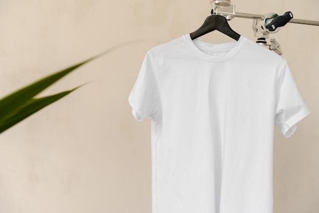 Einfaches weißes baumwoll-t-shirt auf kleiderbügel für ihr design