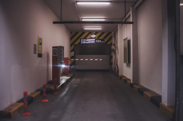 Einfahrt in die tiefgarage oder kostenpflichtiger moderner parkplatz, schranke und kontrollsystem zum einfahren ins auto. eingang der tiefgarage. abstieg ins gebäude mit geschlossenen fensterläden. platz kopieren
