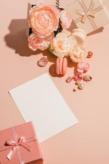 Einfarbiger blumenhintergrund mit modellkarten, einladungen in pfirsichpastellfarbe. minimales begrüßungskonzept