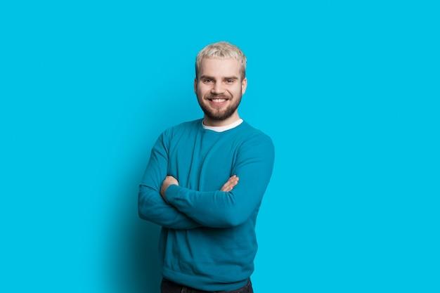 Einfarbiges foto eines kaukasischen mannes mit bart und blondem haar, das mit gekreuzten händen auf einer blauen studiowand aufwirft