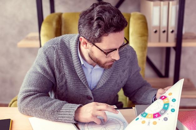 Einfluss auf das schicksal schlauer netter mann, der die zeichnung betrachtet, während er verschiedene sternzeichen studiert