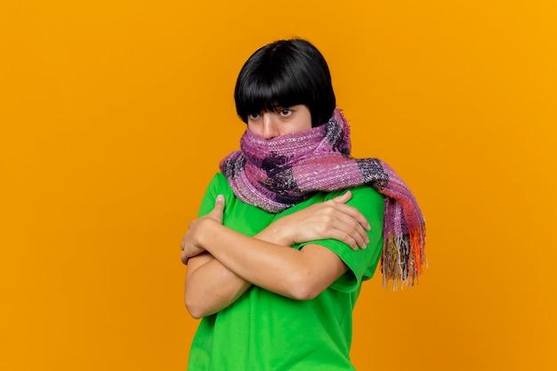 Einfrierende kalte junge kranke frau, die schal, der mund mit schal bedeckt, hält hände, die hände auf den armen gekreuzt halten, die gerade lokal auf orange wand schauen