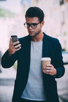 Eingabe einer schnellen nachricht an einen freund. hübscher junger mann in eleganter freizeitkleidung, der eine kaffeetasse hält und auf sein smartphone schaut, während er die straße entlang geht