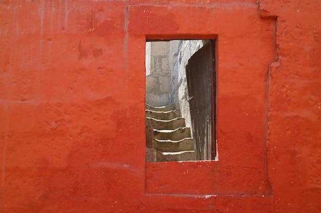 Eingang auf der roten steinwand, die zu dem treppenhaus innerhalb eines altbaus, arequipa, peru führt