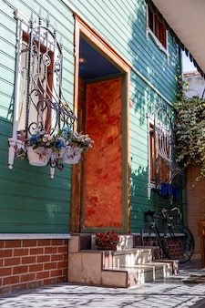 Eingang in ein wohngebäude mit blumen auf fenstern, treppen und geparktem fahrrad in istanbul, türkei