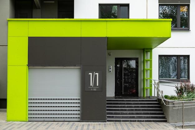 Eingang nummer eins zum neuen frisch gestrichenen mehrfamilienhaus mit rolltor