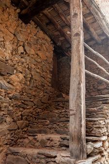 Eingang zu einem haus mit treppe aus schiefer und holzkonstruktion und balken