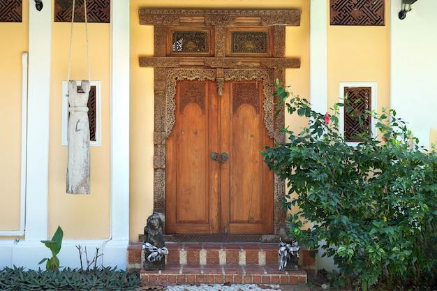 Eingang zum gelben haus mit alten holzfenstern und tür mit geschnitzten mustern. steinweg, der zur treppe führt.