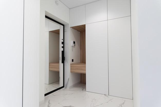Eingangsraum in hellen farben mit naturholzregal eingangsspiegeltür marmorfliesen