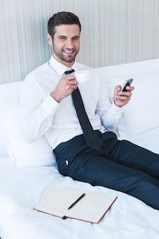 Eingeben von geschäftsnachrichten. fröhlicher junger mann in hemd und krawatte, der kaffee trinkt und das handy hält, während er im bett im hotelzimmer liegt?