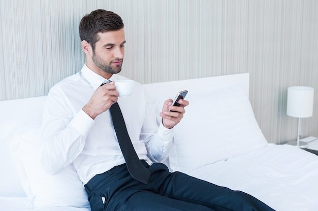 Eingeben von geschäftsnachrichten. selbstbewusster junger mann in hemd und krawatte, der kaffee trinkt und das handy hält, während er im bett im hotelzimmer liegt