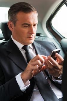 Eingeben von geschäftsnachrichten. selbstbewusster reifer geschäftsmann, der eine nachricht auf seinem smartphone schreibt, während er auf dem rücksitz eines autos sitzt