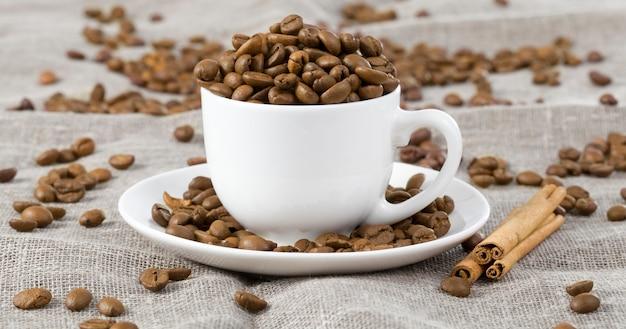 Eingegossen in eine weiße tasse, geröstete, sehr leckere kaffeekörner auf einer tischdecke, daneben duftende und angenehme zimtstangen