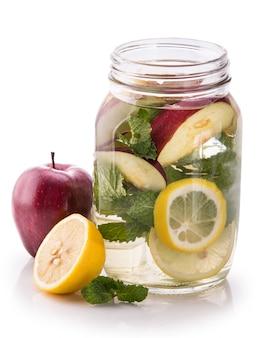 Eingegossenes frisches fruchtwasser aus zitrone, apfel und minze. isolieren