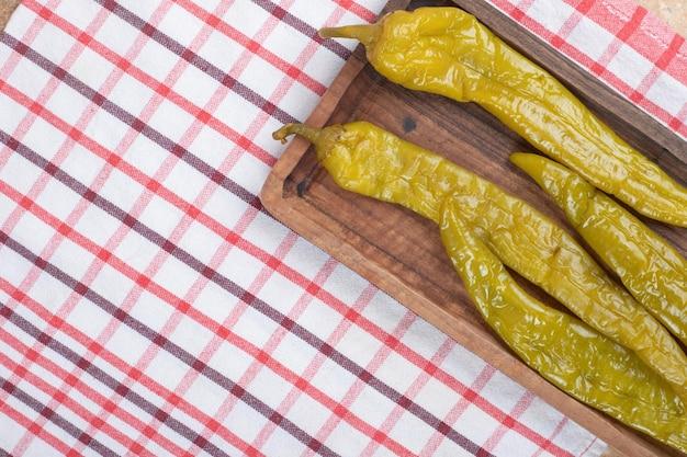 Eingelegte chilischoten auf holzbrett mit tischdecke