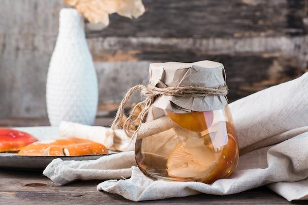 Eingelegte fliegenpilze in einem glas auf einem holztisch. mikrodosierung und alternativmedizin.
