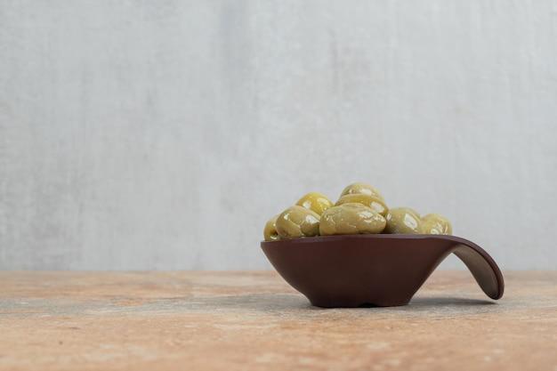 Eingelegte grüne oliven in dunkler schüssel