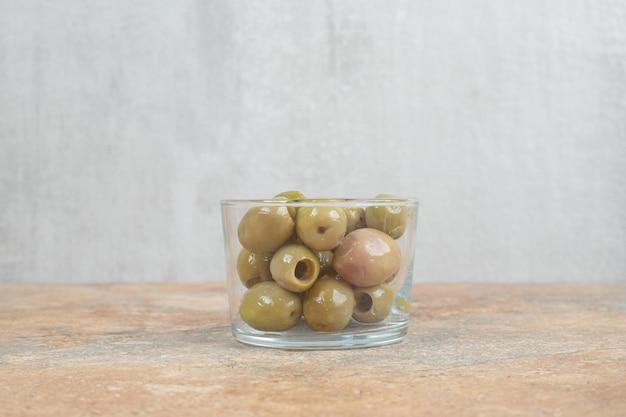Eingelegte grüne oliven in glasschüssel