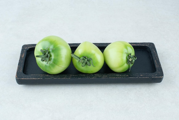 Eingelegte grüne tomaten auf schwarzem teller.