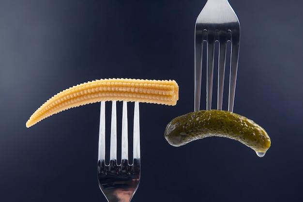 Eingelegte gurke und mais auf einer gabel nahaufnahme. essen und gemüse