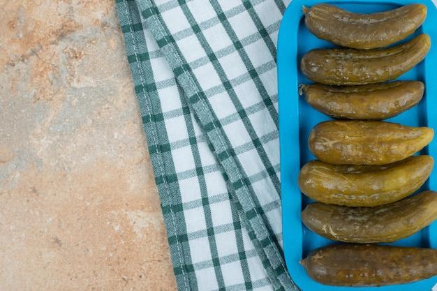 Eingelegte gurken auf blauem teller mit tischdecke