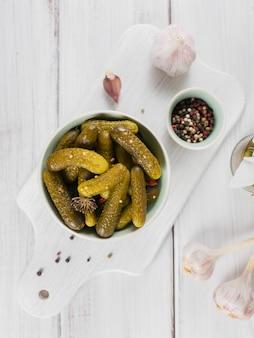 Eingelegte gurken, gewürze und knoblauch auf einem weißen holztisch aufbewahren. gesundes fermentiertes essen. gemüsekonserven.
