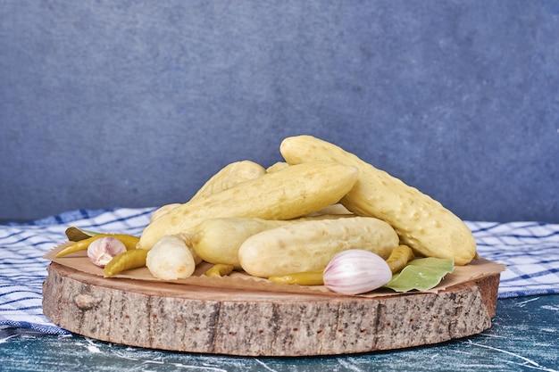Eingelegte gurken, knoblauch, paprika und blatt auf holzteller mit tischdecke.