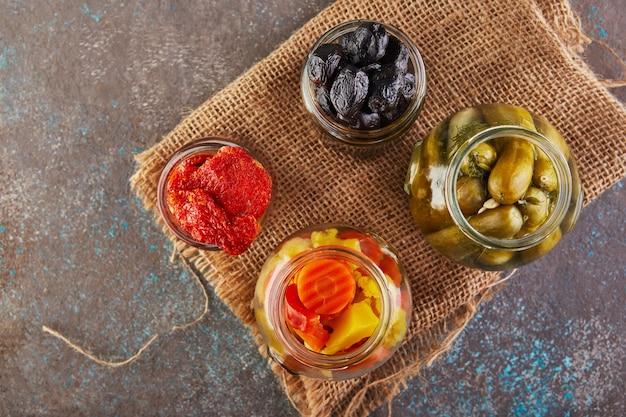 Eingelegte gurken, oliven, getrocknete tomaten und eingelegte karotten in gläsern