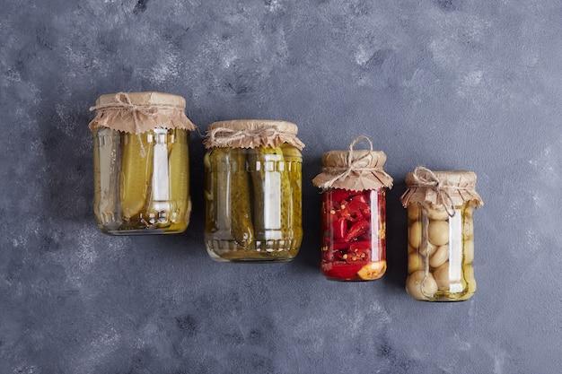 Eingelegte gurken, oliven und paprika in gläsern auf blauem grund.