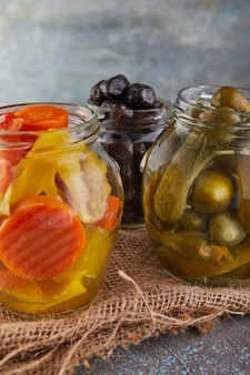 Eingelegte gurken, schwarze oliven und eingelegte karotten in gläsern
