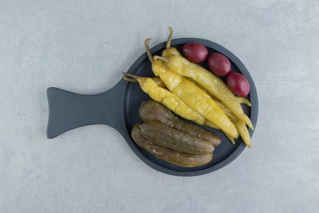 Eingelegte gurken und chilischoten auf dunklem brett.