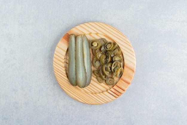 Eingelegte gurken und paprika auf holzplatte.