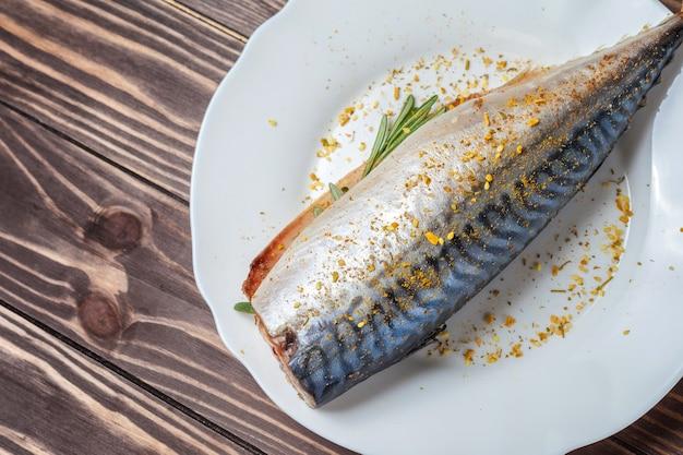 Eingelegte makrele in einem weißen teller. roher unvorbereiteter fisch. traditionelle delikatesse mit meeresfrüchten, gesunde ernährung