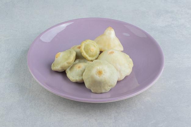 Eingelegte mini-zucchini in einem teller auf der marmoroberfläche