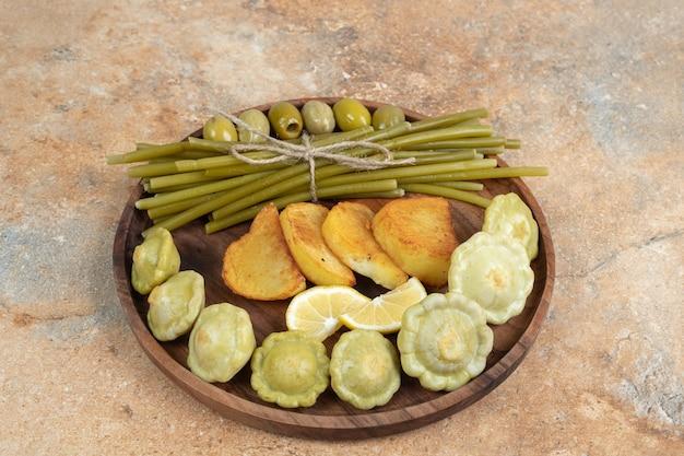 Eingelegte oliven, grüne bohnen und bratkartoffeln auf holzteller