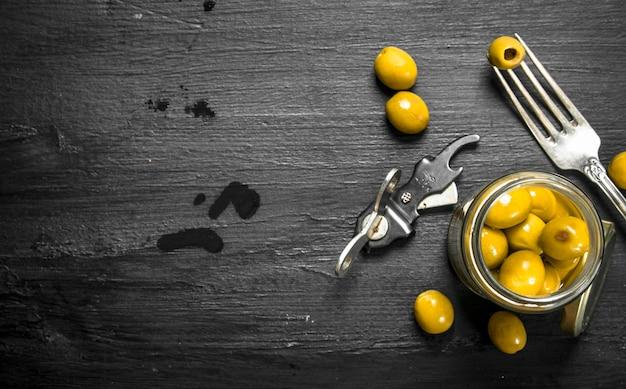 Eingelegte oliven im glas. auf der schwarzen tafel.