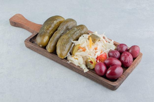 Eingelegte oliven, kohl und gurken auf einem brett auf der marmoroberfläche