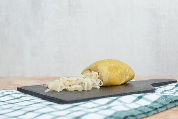 Eingelegte paprikaschoten gefüllt mit sauerkraut auf dunklem brett