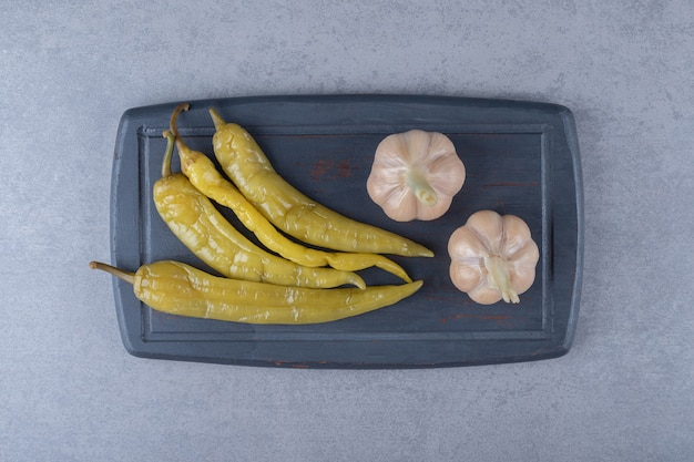 Eingelegte peperoni mit knoblauch, auf dem brett