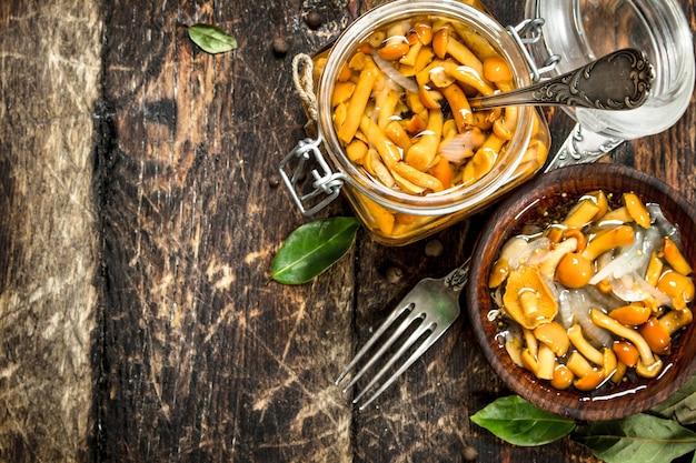 Eingelegte pilze in einer schüssel mit gewürzen und kräutern auf holztisch.