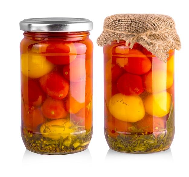 Eingelegte rote und gelbe tomate im glas lokalisiert auf weiß.