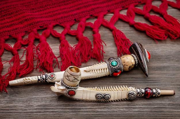 Eingelegte souvenir-tabakpfeifen und rotes plaid der amerikanischen ureinwohner. kopierraum, studioaufnahme.