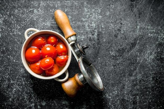 Eingelegte tomaten in einer schüssel. auf dunklem rustikalem hintergrund