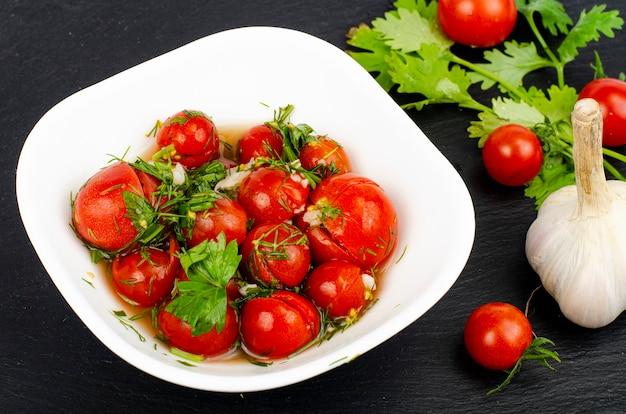 Eingelegte tomaten mit kräutern und knoblauch. studiofoto.