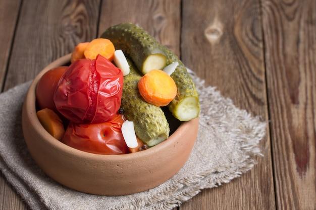 Eingelegte tomaten und gurken in keramik auf einem holztisch.