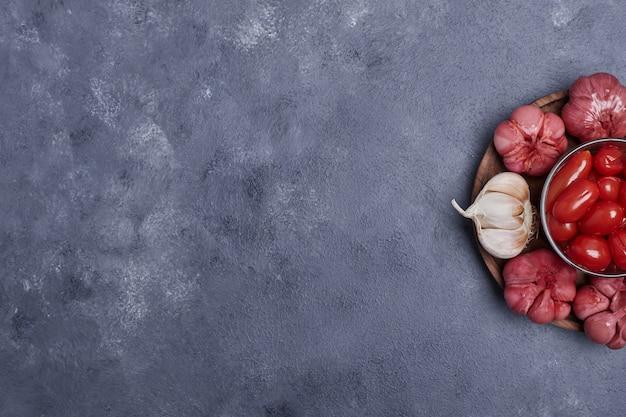 Eingelegte tomaten und knoblauch auf holzteller.