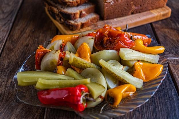 Eingelegte tomatengurke und paprika in einer glasschüssel auf einem holztisch köstliche hausgemachte gurken