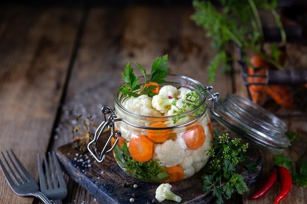 Eingelegter blumenkohl mit karotten in einem glas auf einem dunklen holztisch. fermentiertes essen.