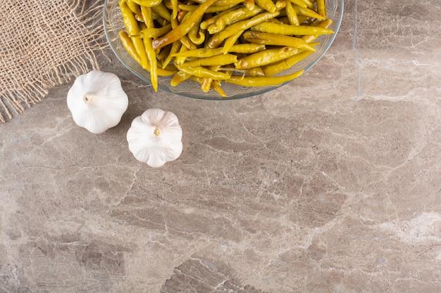 Eingelegter grüner chilipfeffer auf steintisch gelegt.